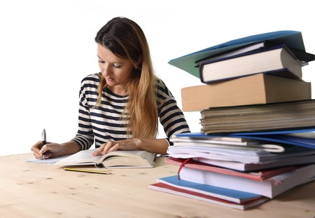 exam: young student girl concentrated studying with textbook at college library desk with piles of books preparing MBA test or exam in academic wisdom and education concept