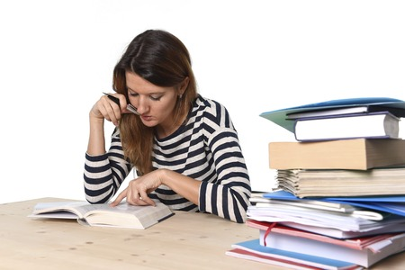 school exam: young student girl concentrated studying with textbook at college library desk with piles of books preparing MBA test or exam in academic wisdom and education concept