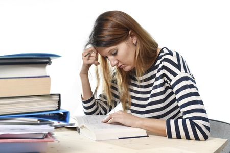 young student girl concentrated studying with textbook at college library desk with piles of books preparing MBA test or exam in academic wisdom and education concept photo