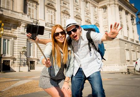 mochila viaje: j�venes amigos hermosa pareja de turistas visitando Espa�a en los estudiantes de intercambio de vacaciones y la toma de fotograf�as palo Autofoto juntos en la ciudad feliz en un d�a soleado en los viajes y el concepto de vacaciones