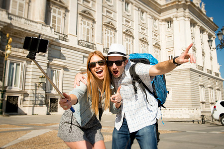 guy with walking stick: young beautiful friends tourist couple visiting Spain in holidays exchange students and taking selfie stick picture together in town happy on sunny day in travel and vacation concept