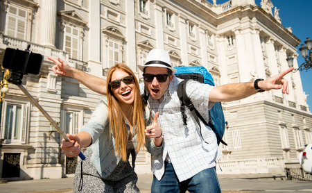 traveller: young beautiful friends tourist couple visiting Spain in holidays exchange students and taking selfie stick picture together in town happy on sunny day in travel and vacation concept
