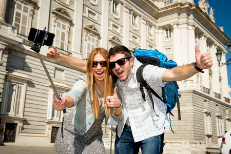 are taking: young beautiful friends tourist couple visiting Spain in holidays exchange students and taking selfie stick picture together in town happy on sunny day in travel and vacation concept
