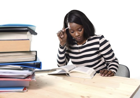 ethnicity: young black African American ethnicity student girl studying pile of books on library desk preparing exam in stress reading textbook concentrated in youth education concept
