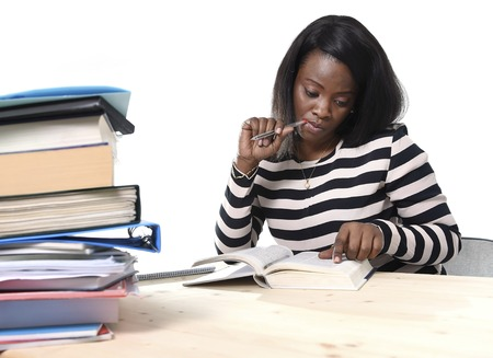 young black African American ethnicity student girl studying pile of books on library desk preparing exam in stress reading textbook concentrated in youth education concept photo