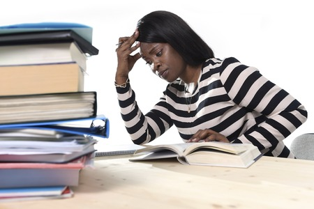 young stressed black African American ethnicity student girl studying pile of books on library desk preparing exam in stress feeling tired and overwhelmed in youth education concept