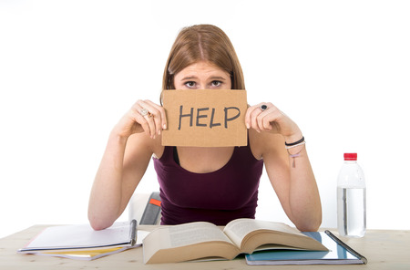 stressed people: young beautiful college student girl studying for university exam in stress asking for help under test pressure sitting on desk with book in youth education concept Stock Photo