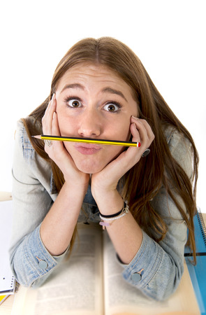 long hours: young beautiful student holding pen between nose and lips as moustache looking funny and playful bored after studying long hours isolated on white background