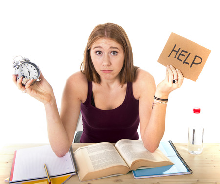 test deadline: young beautiful college student girl studying for university exam in stress asking for help holding alarm clock test deadline time pressure sitting on desk in education concept