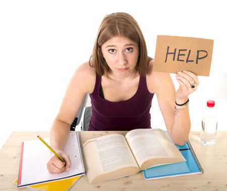 test deadline: young beautiful college student girl studying for university exam in stress asking for help under test pressure sitting on desk with book in youth education concept Stock Photo