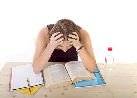 hard: young beautiful college student girl studying busy for university exam  in stress working hard fully concentrated and silent sitting on desk with book in youth education concept