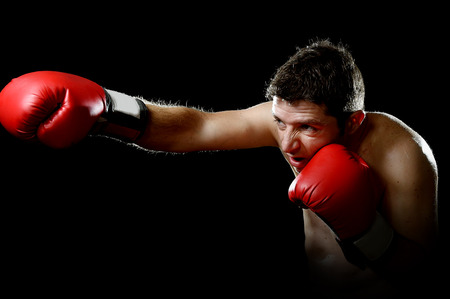 vicious: young aggressive fighter man training shadow boxing at gym with red fighting gloves throwing vicious punch in angry rage face expression isolated on black background