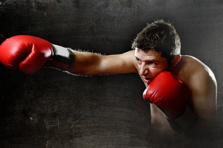 vicious: young aggressive fighter man training shadow boxing at gym with red fighting gloves throwing vicious punch in angry rage face expression isolated on dark grunge dirty background