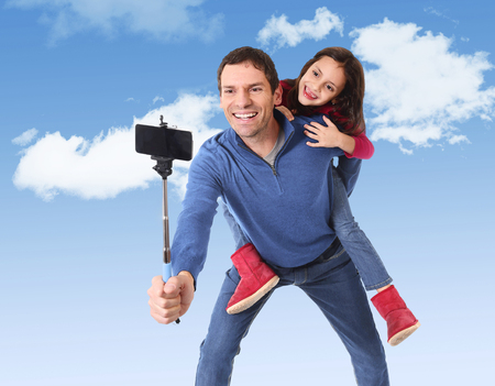 carrying: attractive Brazilian father carrying cute young daughter on his back having fun smiling happy taking stick selfie photo with mobile phone together on a blue sky with clouds