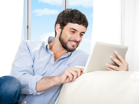 35 years old man: Young attractive Hispanic man at home sitting on white couch using digital tablet or pad looking relaxed smiling at living room enjoying surfing internet watching online movie