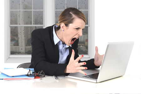 pissed: young attractive businesswoman frustrated and desperate expression at office working on computer laptop in stress at work concept screaming angry with sad rainy window view Stock Photo