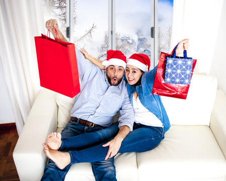 young happy couple wearing Santa hat and casual clothes on Christmas holding shopping bags with presents and gifts sitting on couch at home with snow window landscape photo