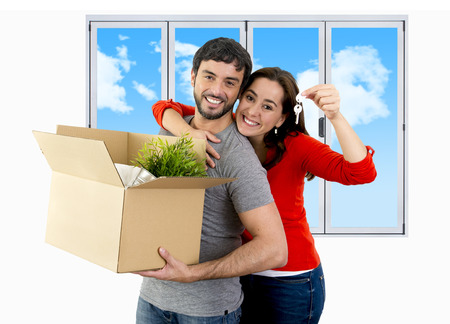real state: young happy Hispanic couple moving together in a new house , flat or apartment carrying cardboard boxes home belongings smiling in housing and real state concept Stock Photo