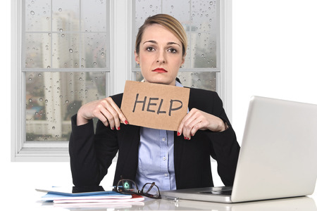 young attractive frustrated businesswoman holding help message overworked at office computer, exhausted, desperate under pressure and stress with rainy sad window view