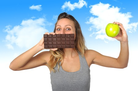 temptation: young attractive sport woman holding apple and chocolate bar in her hands in healthy fruit versus sweet junk food temptation in fitness, body health care and healthy nutrition concept