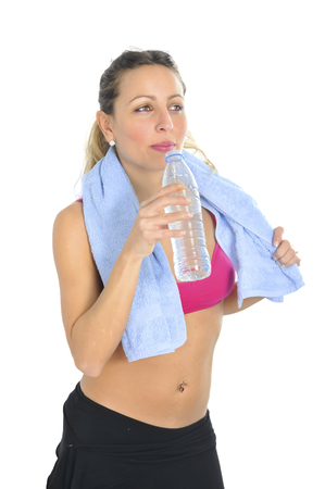 sports bra: young attractive and sexy blond hair woman in sport clothes with towel hanging on neck after gym workout drinking bottle of water in diet, fitness, health and exercise concept Stock Photo