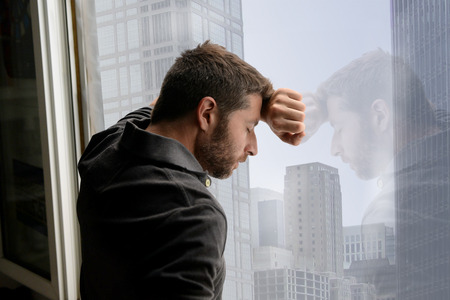 exhausted: young attractive man leaning desperate on window glass at business district home, looking worried, depressed, thoughtful and lonely suffering depression in work or personal problems