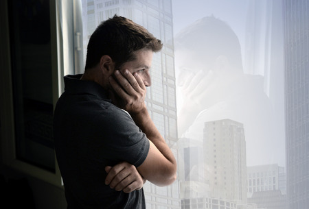 stress: young attractive man leaning desperate on window glass at business district home, looking worried, depressed, thoughtful and lonely suffering depression in work or personal problems