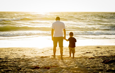 barefoot: Young happy father holding holding hand of little son walking together on the beach with barefoot in sand in front of sea waves, the kid smiling and having fun  with dad in Summer sunset coast