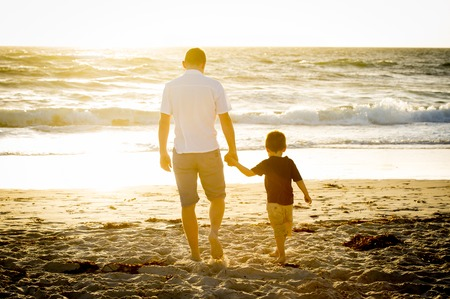 Young happy father holding holding hand of little son walking together on the beach with barefoot in sand in front of sea waves, the kid smiling and having fun  with dad in Summer sunset coast