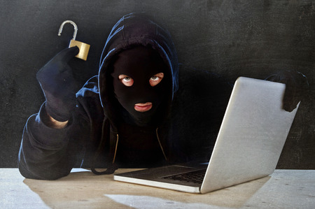 hacker man in black hood and mask with computer laptop holding lock in dangerous dark look hacking system having access to data info and privacy in business digital crack and cyber crime concept 版權商用圖片