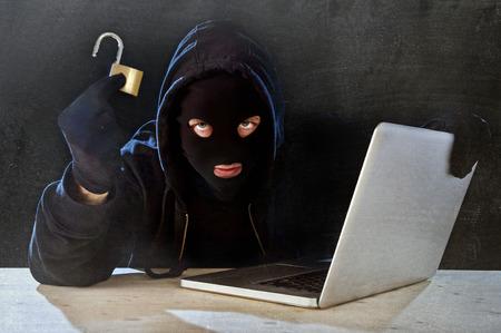 Pirate homme dans cagoule noire et masque avec un ordinateur portable en retenant le blocage dans l'obscurité dangereuse regarder à système ayant accès aux informations de données et la vie privée dans les affaires fissure numérique et le concept de la cybercriminalité de piratage Banque d'images - 39294709