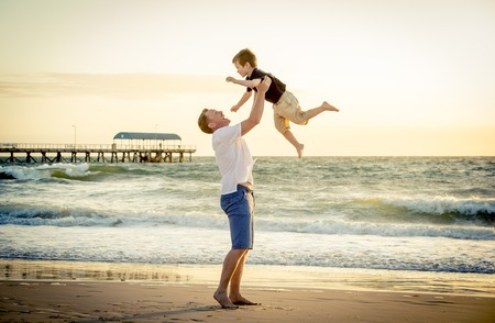 pies descalzos: joven padre feliz sosteniendo en sus brazos el pequeño hijo poniéndolo arriba en la playa en los pies descalzos de pie delante de las olas del mar arena mojada que se divierte con el niño en costa de verano la puesta de sol