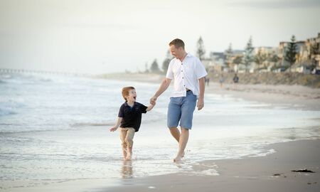 boy shorts: young happy father holding hand of little son walking together on the beach with barefoot in sand in front of sea waves, the kid smiling and having fun with dad in Summer coast holidays