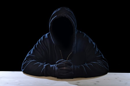 maniac: criminal or terrorist man in gloves, black hood and thief mask looking dangerous with hidden identity in secret illegal activity and crime concept with creepy scary terrorist and maniac look