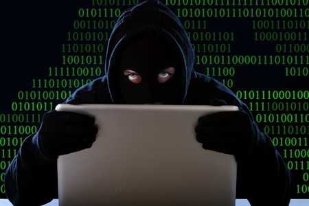 intruder: hacker man in black hood and mask with computer laptop in dangerous dark look hacking system having access to data info and privacy in business digital intruder and cyber crime concept