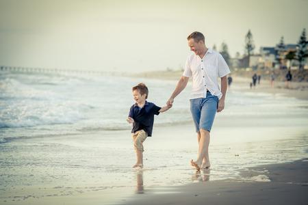 pies descalzos: joven feliz padre de la mano del pequeño hijo caminando juntos en la playa con los pies descalzos en la arena frente a las olas del mar, el chico sonriendo y divirtiéndose con papá en las vacaciones de verano de la costa Foto de archivo