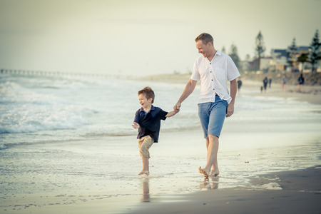 barefoot blonde: young happy father holding hand of little son walking together on the beach with barefoot in sand in front of sea waves, the kid smiling and having fun with dad in Summer coast holidays