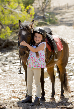 ponies: sweet beautiful young girl 7 or 8 years old hugging head of little pony horse smiling happy wearing safety jockey helmet posing outdoors on countryside in summer holiday