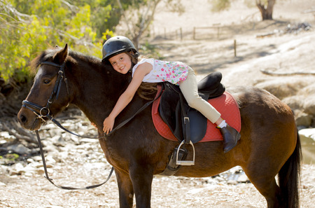 8 years old: sweet beautiful young girl 7 or 8 years old riding pony horse hugging and smiling happy wearing safety jockey helmet posing outdoors on countryside in summer holiday