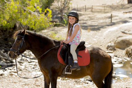 riding helmet: sweet beautiful young girl 7 or 8 years old riding pony horse and smiling happy wearing safety jockey helmet posing outdoors on countryside in summer holiday Stock Photo