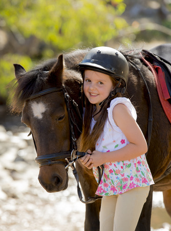 bridle: sweet beautiful young girl 7 or 8 years old holding bridle of little pony horse smiling happy wearing safety jockey helmet posing outdoors on countryside in summer holiday