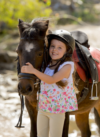 sweet beautiful young girl 7 or 8 years old hugging head of little pony horse smiling happy wearing safety jockey helmet posing outdoors on countryside in summer holiday