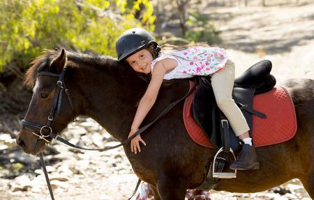 美しい甘い少女 7 または 8 歳ポニー馬ハグと笑って幸せに乗って安全ジョッキー ヘルメット屋外でポーズの田舎で夏休みに身に着けています。