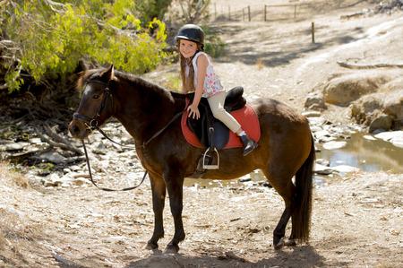 Lief mooi jong meisje 7 of 8 jaar oud riding pony paard en glimlachend gelukkig dragen veiligheid jockey helm poseren buiten op platteland in de zomer vakantie Stockfoto - 39523736