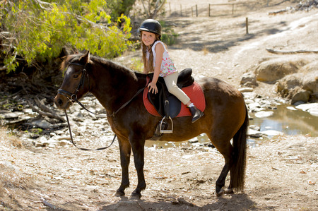 horse riding: sweet beautiful young girl 7 or 8 years old riding pony horse and smiling happy wearing safety jockey helmet posing outdoors on countryside in summer holiday Stock Photo