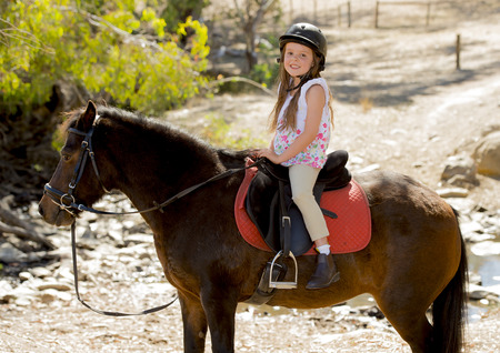 sweet beautiful young girl 7 or 8 years old riding pony horse and smiling happy wearing safety jockey helmet posing outdoors on countryside in summer holiday Stock Photo