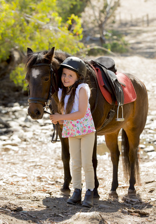 8 years old: sweet beautiful young girl 7 or 8 years old holding bridle of little pony horse smiling happy wearing safety jockey helmet posing outdoors on countryside in summer holiday