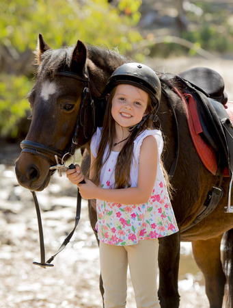7 8 years: sweet beautiful young girl 7 or 8 years old holding bridle of little pony horse smiling happy wearing safety jockey helmet posing outdoors on countryside in summer holiday