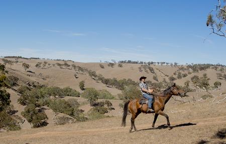 uomo a cavallo: giovane istruttore cavallo o allevatore di bestiame a cavallo l'animale che indossa cappello e cavaliere stivali da cowboy che sembra freddo durante l'assunzione di un giro in campagna estiva paesaggio Archivio Fotografico
