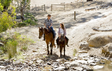 cowgirl hat: young American Australian man as father or horse instructor of young girl or  teen daughter riding little pony wearing cowgirl hat in countryside Summer vacation ride Stock Photo